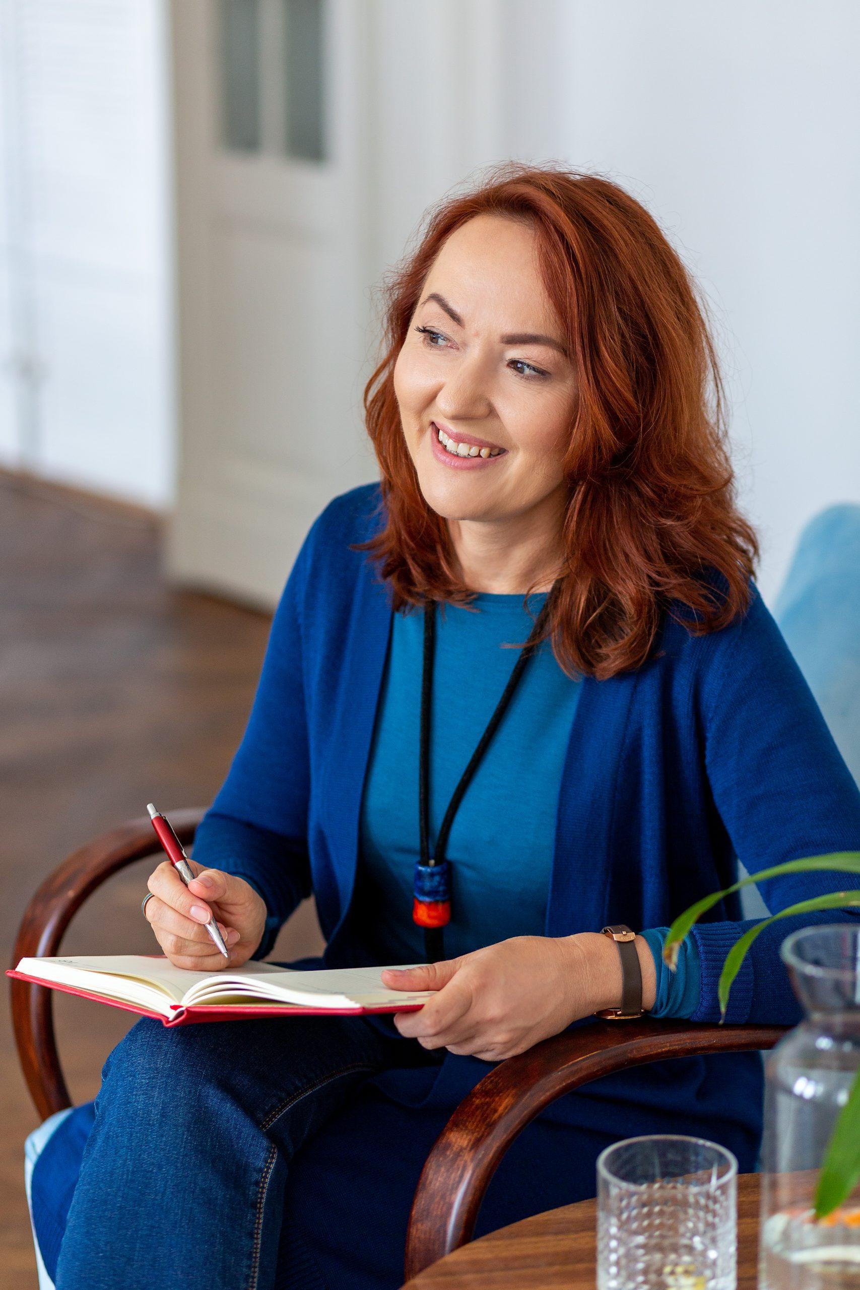 Zdjęcie przedstawia uśmiechniętą Annę Witkiewicz coacha kariery, siedzącą na fotelu