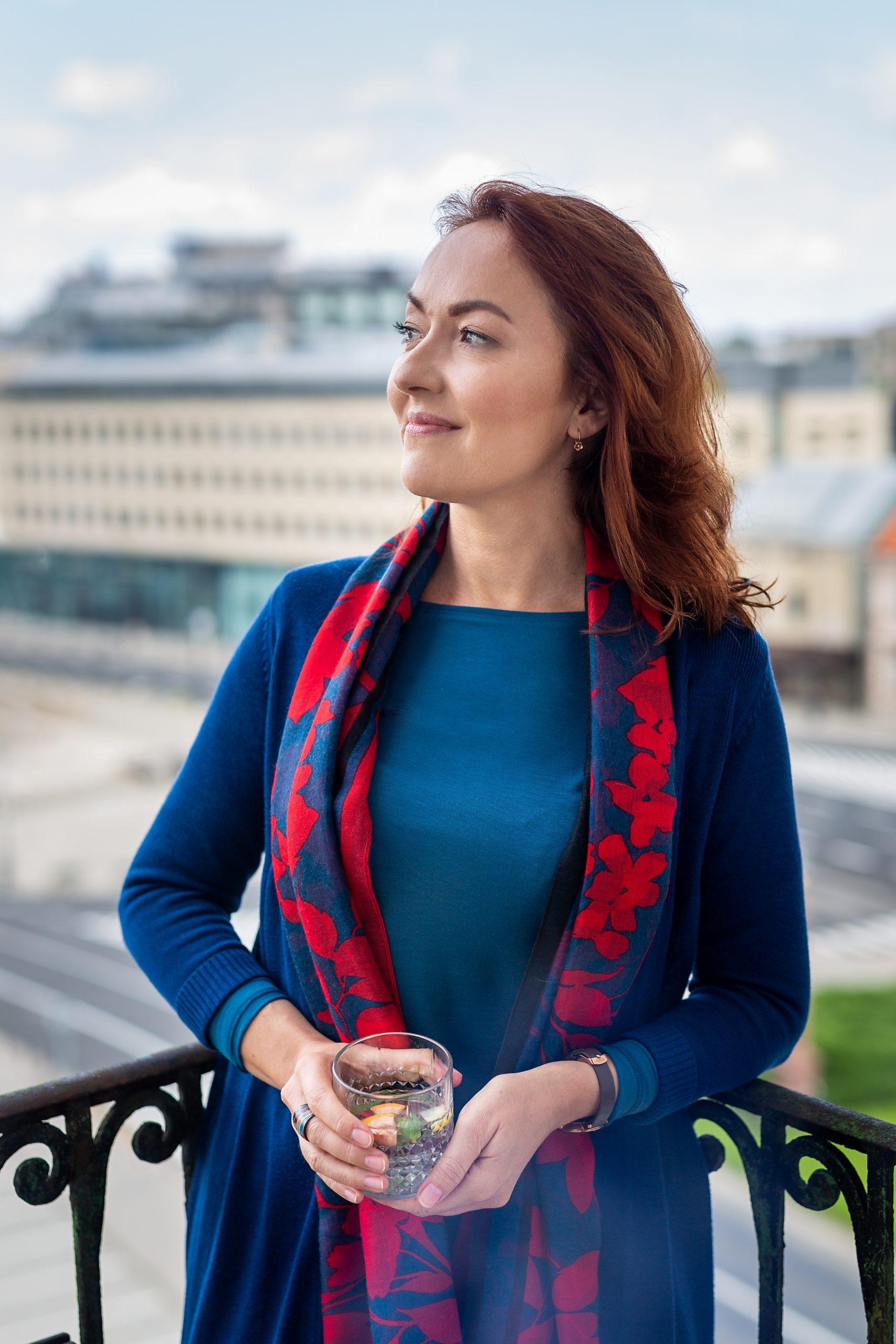 Zdjęcie przedstawia Annę Witkiewicz coacha kariery, która w nieformalnej stylizacji stoi na balkonie i patrz w dal
