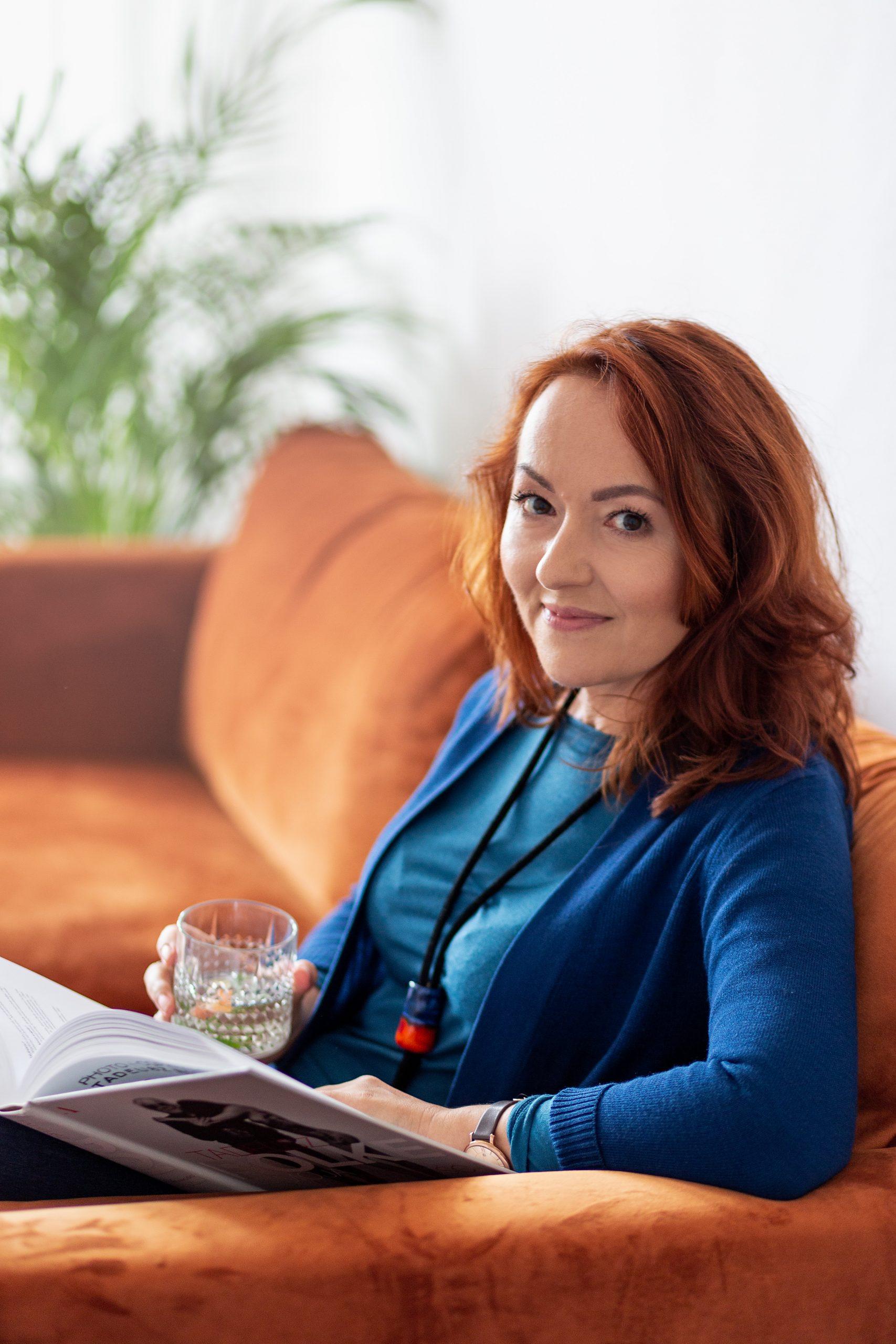Anna Witkiewicz w nieformalnej stylizacji trzymająca książkę o tematyce coachingowej