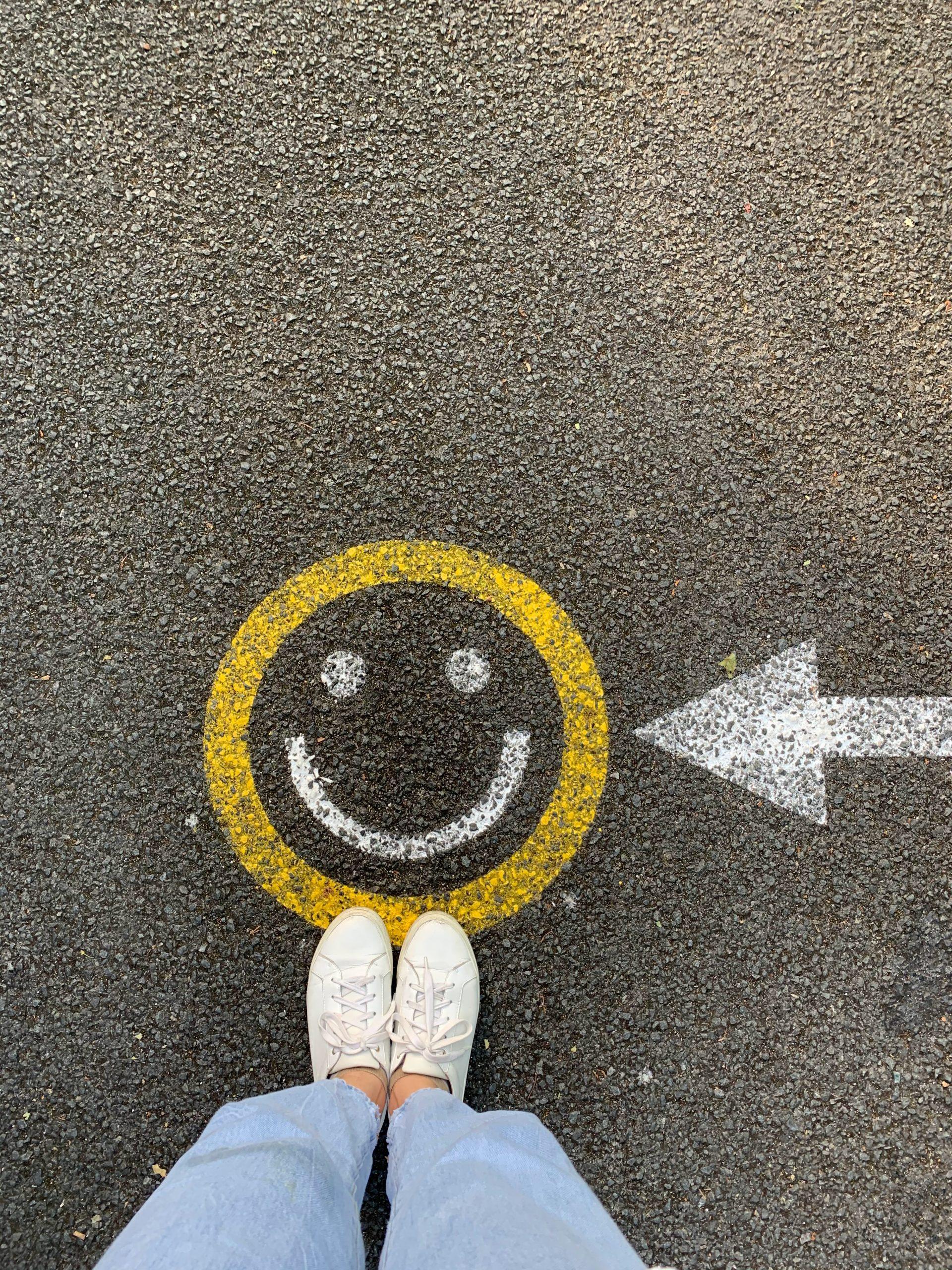 Zdjęcie przedstawia strzałkę wskazującą na rysunek z uśmiechem